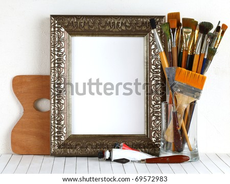 Picture gold frame with a palette and paintbrushes - stock photo