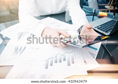 Picture man touching modern tablet screen.Trader manager working new private banking project office.Using electronic device.Graphic icons,stock exchanges reports table. Horizontal.Film effect