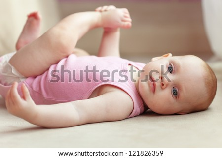 Picture of a baby lying in bed - stock photo
