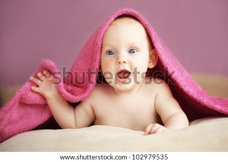 Picture of a baby lying under towel in bed - stock photo