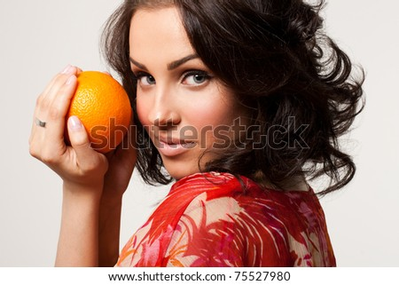 Picture of a beautiful young woman holding orange in hands - stock photo