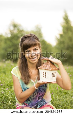 Picture of a beautiful young woman offering a house