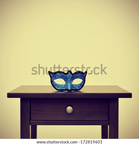 picture of a blue carnival mask on a desk, with a retro effect - stock photo