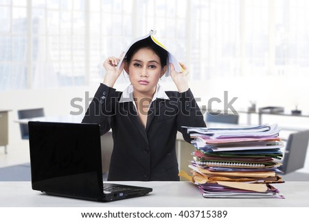Picture of a bored female worker doing her job with a laptop and a pile of document in the office - stock photo