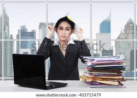 Picture of a bored female worker working in the office with a laptop and document while putting a paperwork on her head - stock photo