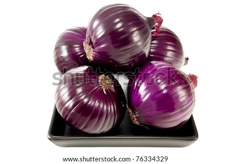 Picture of a bunch of red onions on a black plate - stock photo