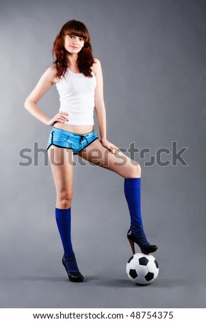 Picture of a charming young girl in a blue shorts and with a soccer ball.