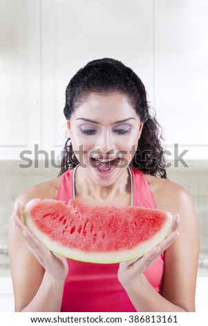 Picture of a cheerful Indian woman holding a slice of fresh watermelon in the kitchen at home - stock photo