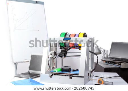 Picture of a 3D-printer standing on the table with laptops and flip chart board on the background in a laboratory - stock photo
