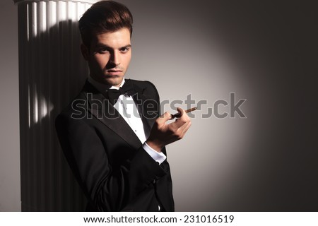 Picture of a elegant business man leaning on a column while looking at the camera with a cigarette in his right hand. - stock photo
