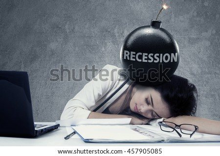 Picture of a female worker sleeping on the table with text of Recession on the bomb at her head - stock photo