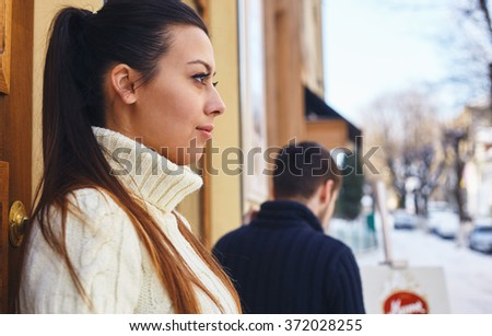 Picture of a girl, standing outside the cafe, looking away and a boy going away at the background.