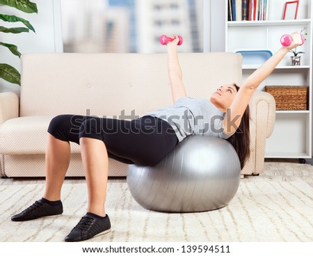 Picture of a girl working out in living room with an exercise ball. - stock photo