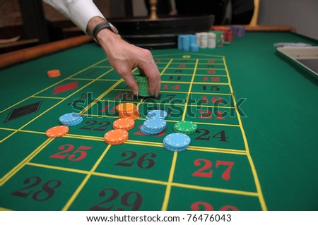 Picture of a hand betting with green, orange and blue chips