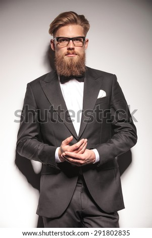 Picture of a handsome business man looking at the camera while holding his hands together. - stock photo