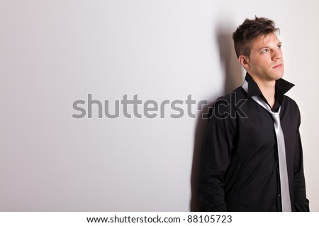 Picture of a handsome casually man leaning against the wall - stock photo