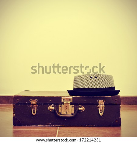 picture of a hat on an old suitcase, with a retro effect - stock photo