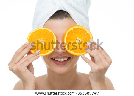 Picture of a laughing woman holding slices of orange