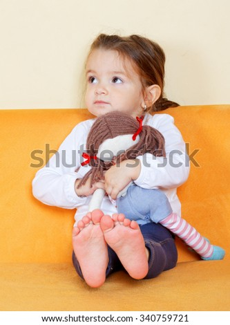 Picture of a little girl holding her doll - stock photo