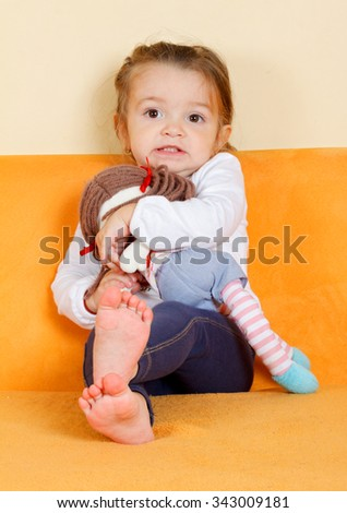 Picture of a little scared girl holding her doll - stock photo