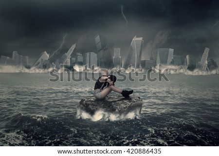 Picture of a lonely girl sitting on the rock at the sea and need help - stock photo