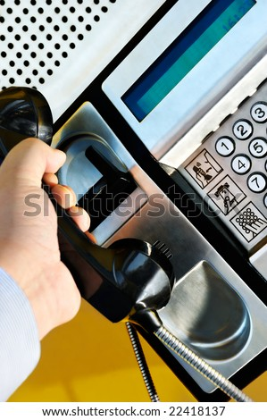 Picture of a male hand retrieving the handset of a public telephone in order to make a call - stock photo
