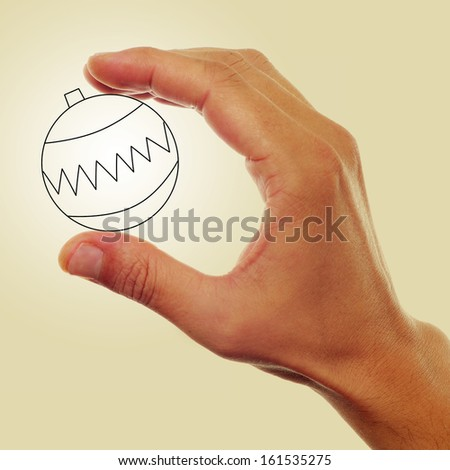 picture of a man hand holding an illustration of a christmas ball on a beige background, with a retro effect