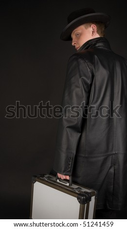 Picture of a man in black  with suitcase
