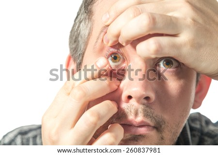 Picture of a man putting on a contact lens