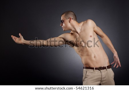 picture of a muscular man with sunglasses reaching out - stock photo