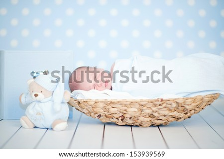 Picture of a newborn baby curled up sleeping in a basket on a blanket - stock photo