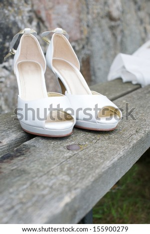 Picture of a pair of white wedding shoes on a bench - stock photo