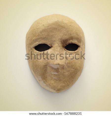 picture of a papier-mache mask on a beige background, with a retro effect - stock photo