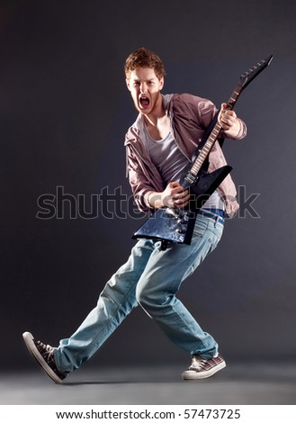 picture of a passionate guitarist playing on dark background - stock photo