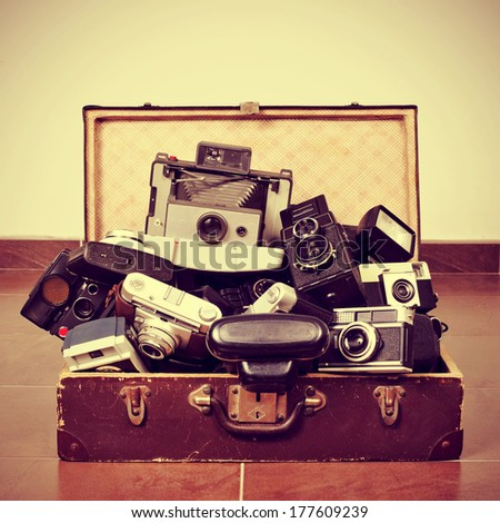 picture of a pile of old cameras in an old suitcase, with a retro effect - stock photo