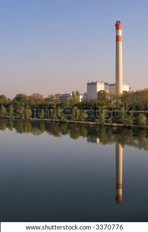 Picture of a power station - its mirror image in a river can be seen.