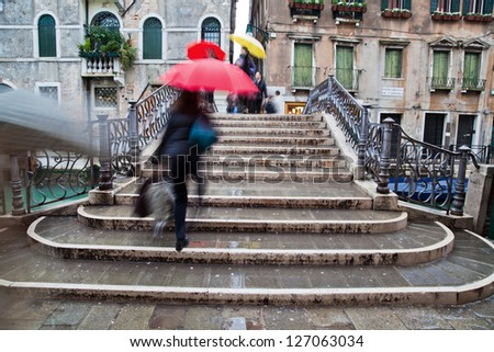 picture of a rainy day in Venice with an old bridge and crossing people with umbrellas