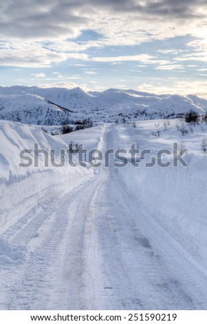 Picture of a road covered with snow, with mountains in the back