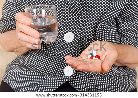 Picture of a senior woman pills holding pills and glass of water - stock photo