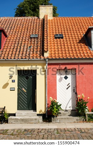 Picture of a small yellow house and a small red house