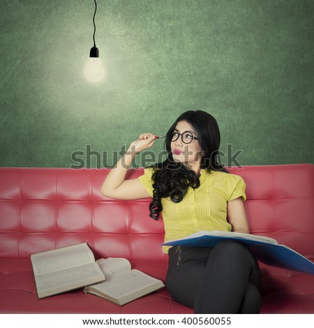Picture of a smart female student reading books while sitting on the sofa and looking at a bright light bulb