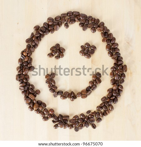 Picture of a smiley face made of coffee beans - stock photo
