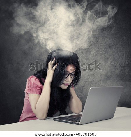 Picture of a stressful young businesswoman with smoke coming out of her head while working with a laptop - stock photo