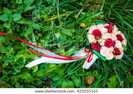 picture of a wedding bouquet , Wedding bouquet of red and white roses lying on grass