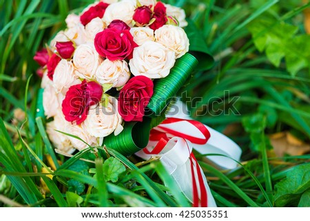 picture of a wedding bouquet , Wedding bouquet of red and white roses lying on grass - stock photo