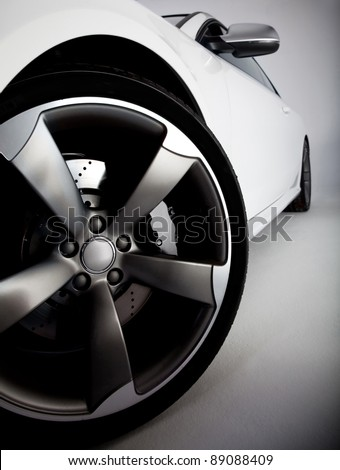 Picture of a white sports carfocusing on the tire - stock photo