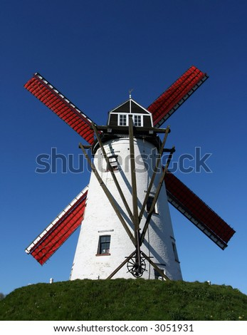 Picture of a windmill with a clear blue sky at the background. Picture taken near Bruges, Belgium.