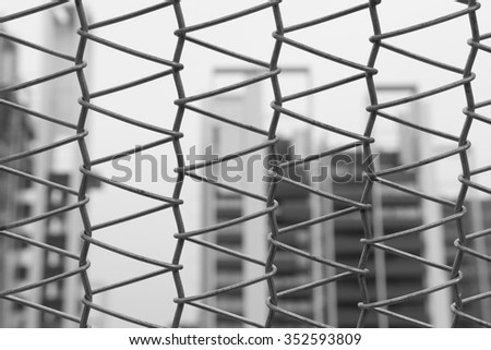 Picture of a wire mesh woven into triangles and the background of buildings. - stock photo