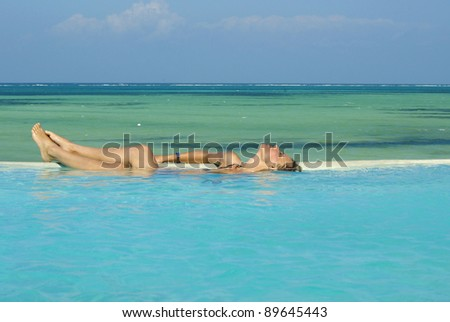 Picture of a woman sunbathing in a swimming-pool - stock photo