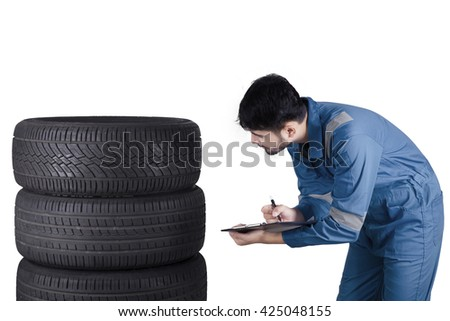 Picture of a young Arabian mechanic checks the tires while writing on the clipboard, isolated on white background - stock photo